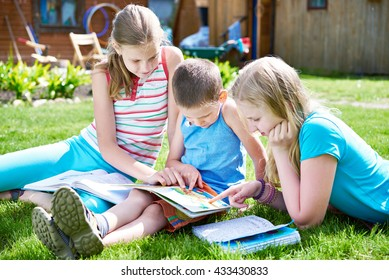 Friends reading book outdoors on grass in summer day