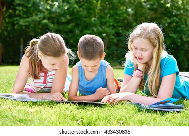 Friends reading books outdoori on grass in summer day