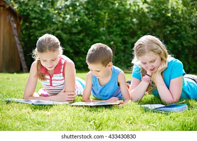 Friends reading books outdoors on grass in summer day
