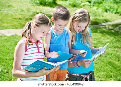 Friends reading books outdoors on nature in summer day