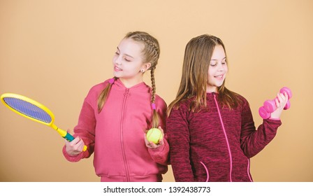 Friends ready for training. Ways to help kids find sport they enjoy. Girls cute kids with sport equipment dumbbells and tennis racket. We love sport. Child might excel in completely different sport.