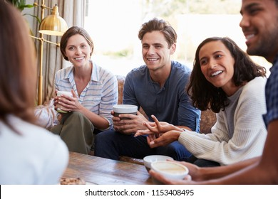 Friends relaxing around a table at a coffee shop, close up