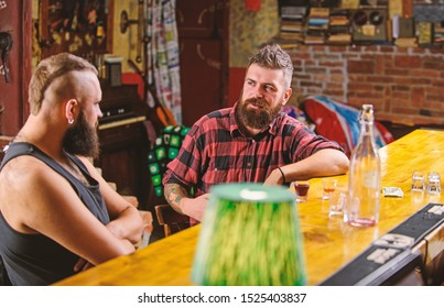 Friends relaxing in bar or pub. Hipster bearded man spend leisure with friend at bar counter. Men relaxing at bar. Strong alcohol drinks. Friday relaxation in bar. Opening hours till last visitors.