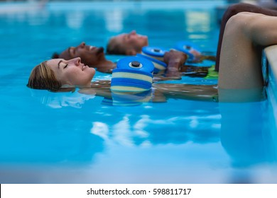Friends relaxing during aqua fitness class. Young beautiful people floating on water surface of swimming pool with plastic dumbbells for aqua aerobics