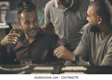 Friends resting in bar after work, communicating and drinking alcoholic beverages. Man in shirt holding glass of brandy or scotch. Friends looking at each other and laughing.