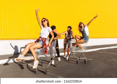 Friends ride on carts, near the supermarket, a great pastime, a group of young people rides on carts, couples in love have fun in Sunny weather
