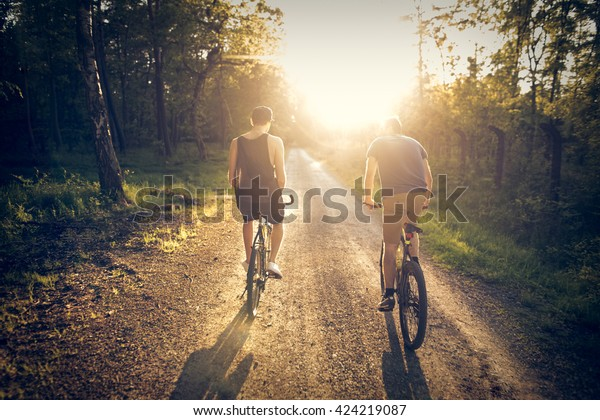 Friends riding on bicycles through the forest during sunset