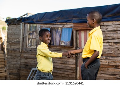 friends shaking hands while standing infront of a shack.