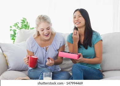 Friends sharing a box of chocolates and laughing at home on the couch