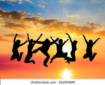 Friends Silhouettes Jumping over Sunset