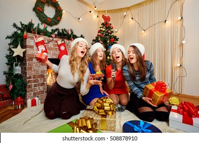 Friends sing karaoke at Christmas, New Year. Four beautiful girls in caps of Santa Claus singing with a microphone in the room with the decor.