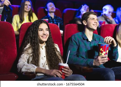 Friends sit and eat popcorn together while watching movies in a movie theater