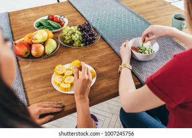 Friends sit at table, talk and eat vegetables by hands.