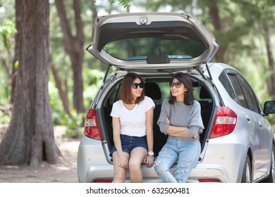 Friends sit talking in the open back of a car