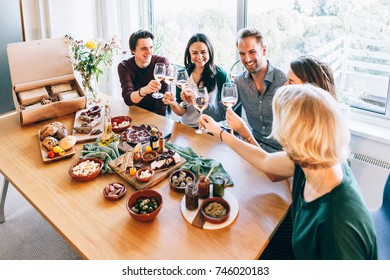 friends sitting around a table having fun with wine and food