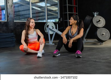 Friends sitting in the gym talking and smiling after training- fitnes hispanic women