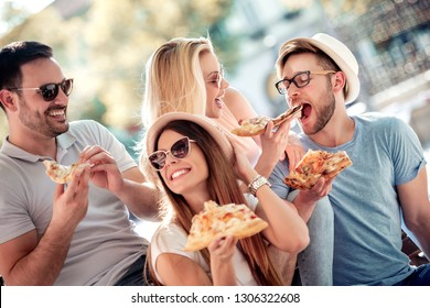 Friends sitting on the bench and eating pizza, having fun outdoors. Dating,people, food and lifestyle concept.