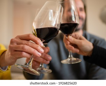 friends sitting on the couch at home toasting with glasses of red wine at home