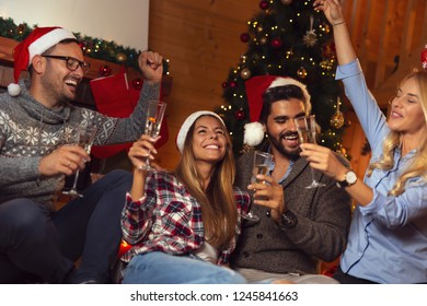 Friends sitting on the floor next to a nicely decorated Christmas tree and making a toast with glasses of champagne. Focus on the girl in the middle