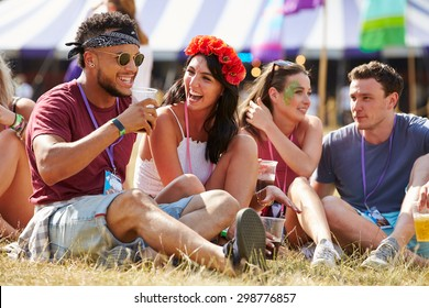 Friends sitting on the grass talking at music festival