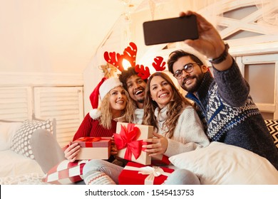Friends sitting on a large bed, taking a selfie; enjoying, happy, smiling