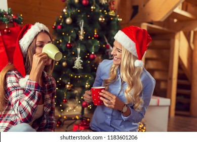 Friends sitting on the living room floor next to a nicely decorated Christmas tree on a Christmas morning, drinking coffee and having fun. Focus on the girl on the right