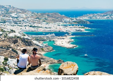 Friends sitting on a rocky outcrop overlooking the old town of Mykonos, Greece, Europe.