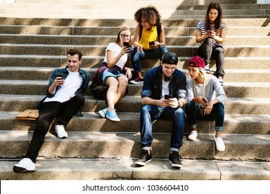 Friends sitting on the staircase using smartphones together and chilling