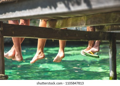 Friends sitting on a wooden pontoon with their legs dangling