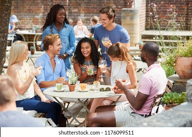 Friends Sitting At Table In Pub Garden Enjoying Drink Together