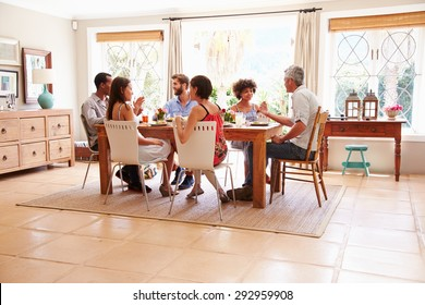 Friends sitting at a table talking during a dinner party