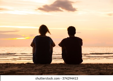 friends sitting together on the beach and watching sunset, friendship concept