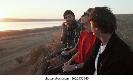 Friends skateboarders smoking joint with weed at seashore at sunset