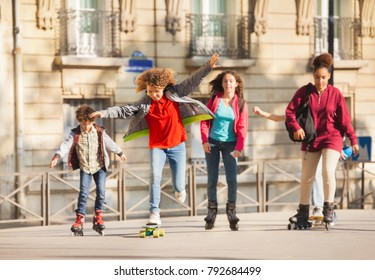 Friends skateboarding and rollerblading in city