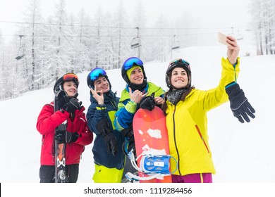 Friends with ski and snowboard taking a selfie on the slopes after skiing. Mountain ski resort with ski lift on background and people, a group of best friends, having fun in winter with snow.
