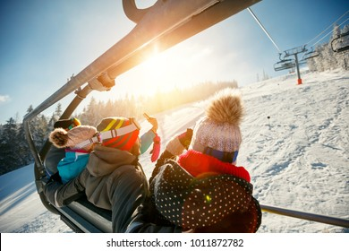 friends skiers and snowboarders on ski lift in the mountain at winter vacations back view