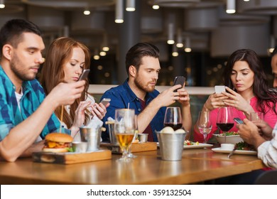 friends with smartphones dining at restaurant