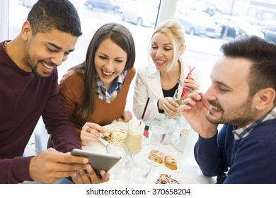 Friends smiling and sitting in a cafe, drinking coffee and enjoying together