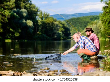 Friends spend nice time at riverside. Beautiful evening riverside. Men at riverside catching fish. Teaching fishing. Sharing his secrets. Experienced fisherman show tips son. Transferring knowledge.