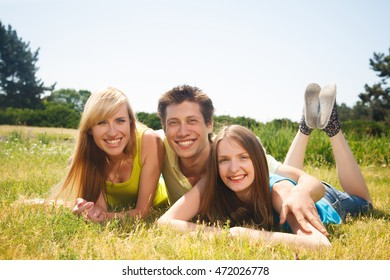 Friends spend their time outdoors or picnic. Group of young people express positivity while laying on the green grass.