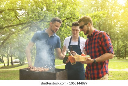 Friends spending time in nature and having barbecue.