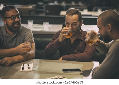 Friends spending time together in bar after work. Man in spectacles smiling and looking at his friends. Two men drinking alcohol beverages, delicious scotch, rum or brandy.