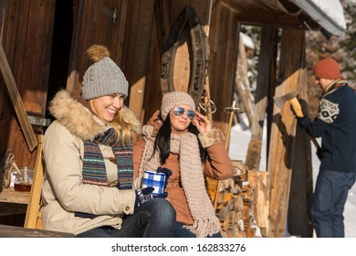 Friends spending winter holiday on mountain cottage enjoy sunny day
