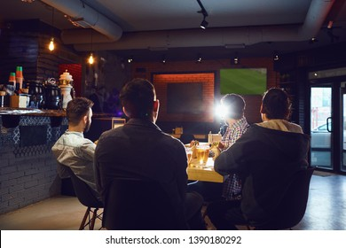 Friends in the sports bar watching TV.