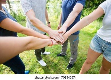 Friends Stacking Hands While Standing On Field In Forest