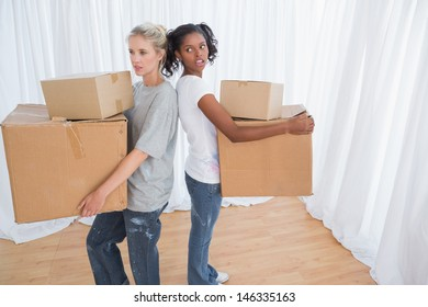 Friends standing back to back holding moving boxes in their new home