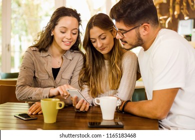 Friends studying together and watching something on the phone