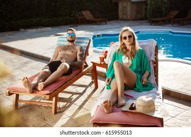 Friends sunbathing, lying on chaises near swimming pool.