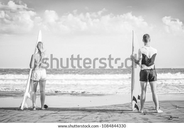 Friends surfers standing on the beach with surfboards preparing to surf on high waves - Healthy couple surfing together - Black and white editing - Concept of sporty people lifestyle