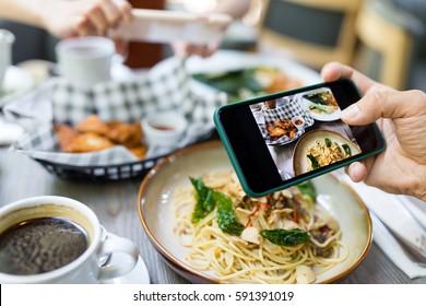 在餐厅用手机拍照的朋友